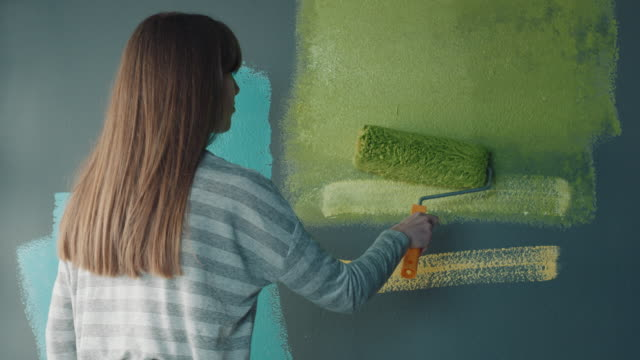 woman painting the walls at home by herself - paint roller stock videos & royalty-free footage