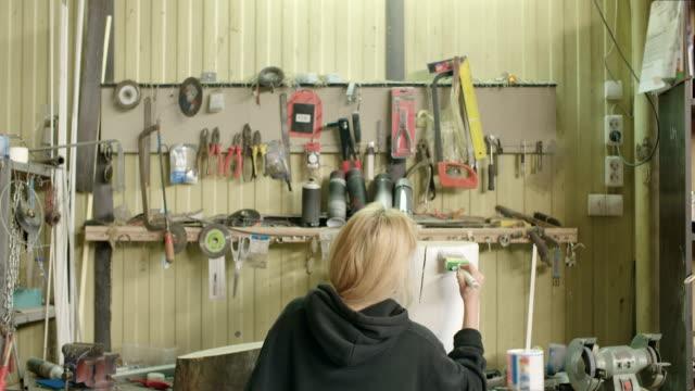 Woman Painting Tree Stump In Workshop