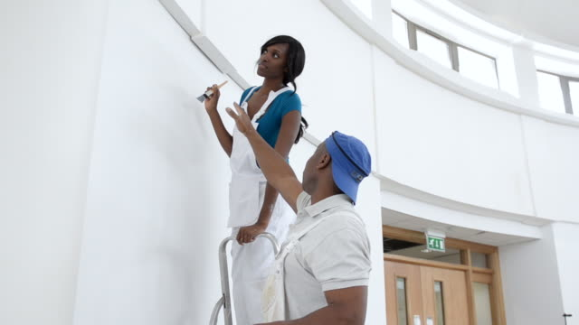 ms woman painting wall and man giving instructions / london, england, united kingdom - instructions stock videos and b-roll footage