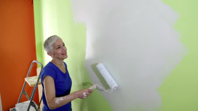 woman painting wall - one mature woman only stock videos & royalty-free footage