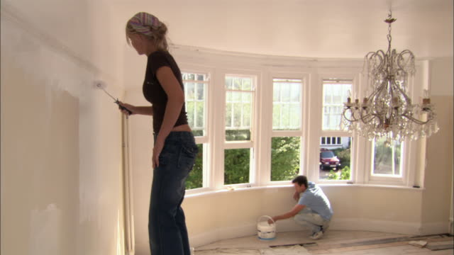 Woman painting wall with paint roller as man crouches and paints wall under windowsill