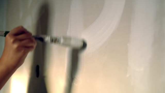 woman painting white letters on wall, slow motion - paintings stock videos and b-roll footage
