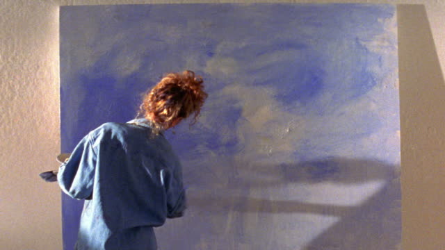 MS REAR VIEW woman painting with blue paint on large canvas on wall