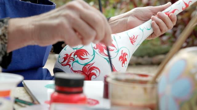donna dipinge una calabash in giardino - zucca legenaria video stock e b–roll