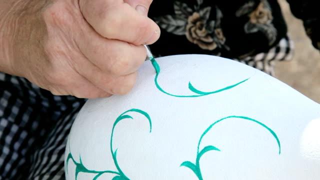 woman paints a calabash