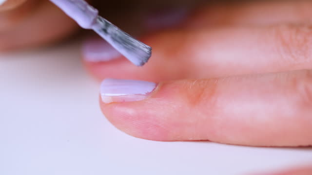 cu woman paints fingernails lilac - human hand stock videos & royalty-free footage