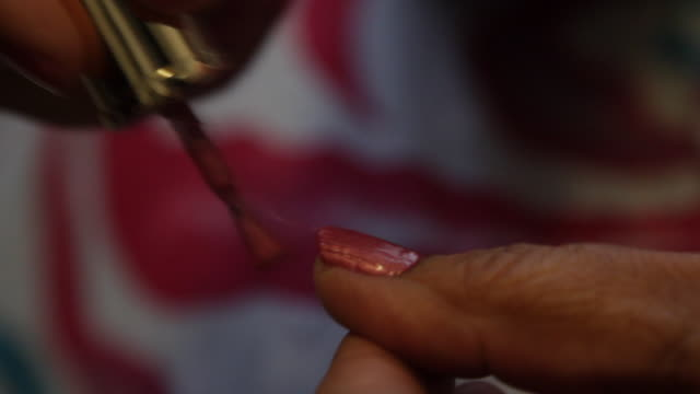 a woman paints her thumb nail with pink polish - sich verschönern stock-videos und b-roll-filmmaterial