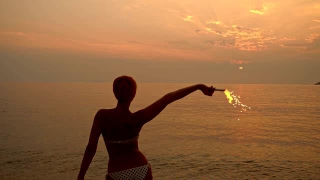 slo mo donna festa con candela magica sulla spiaggia - riva dell'acqua video stock e b–roll