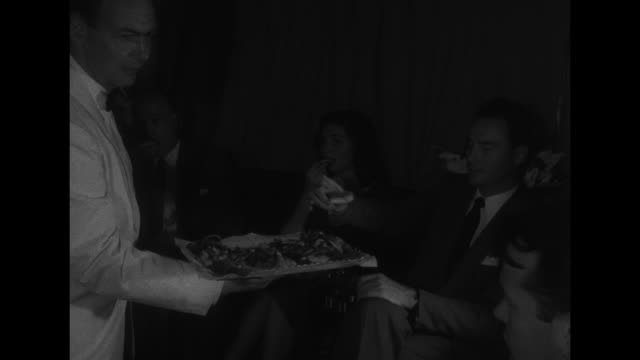 woman passenger being served dinner by flight attendant / woman and woman sitting next to her look at meal she has been served / shot of food trays... - galeere stock-videos und b-roll-filmmaterial