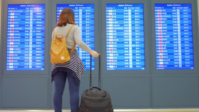 vidéos et rushes de passager de femme vérifiant son vol sur téléphone mobile avec jury de départ numérique avant le check-in à l'aéroport terminal de départ - billboard
