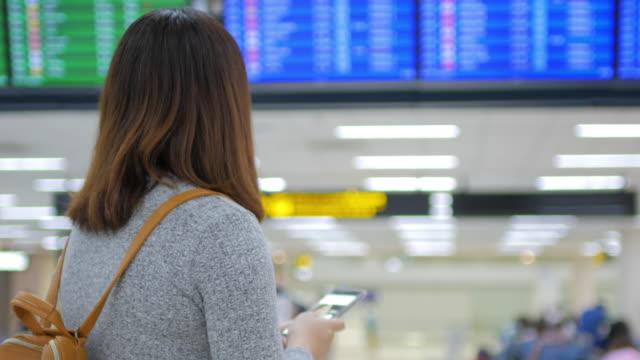 stockvideo's en b-roll-footage met vrouw passagier controle van haar vlucht op mobiele telefoon met digitale vertrek plaat voor het inchecken op de luchthaven van vertrek-terminal - passenger