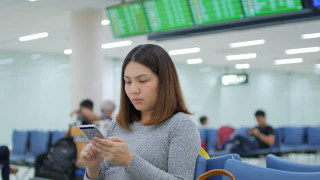 Woman passenger checking her flight on mobile phone with digital departure board before check in at departure terminal airport