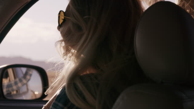Woman passenger in car enjoying wind blowing hair and arm out window / Hanksville, Utah, United States