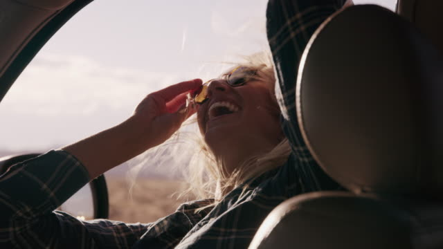 vídeos y material grabado en eventos de stock de woman passenger in car laughing and enjoying wind blowing hair / hanksville, utah, united states - retrovisor exterior