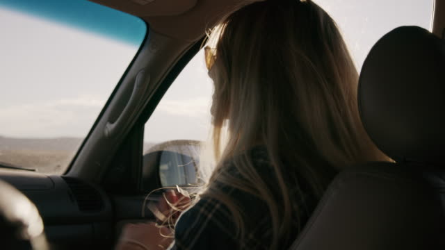Woman passenger listening to music in car and dancing in slow motion / Hanksville, Utah, United States