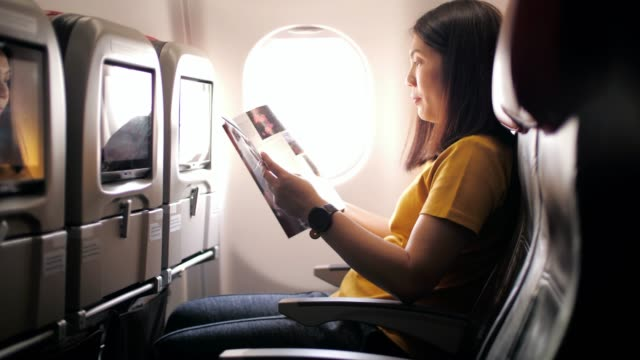 kvinna passenger reading magazine och koppla av på flyget i flyg plan, slow motion - kupe bildbanksvideor och videomaterial från bakom kulisserna