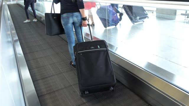 woman passenger traveler with luggage on moving sidewalk at airport / train station going on a trip - carry on luggage stock videos and b-roll footage