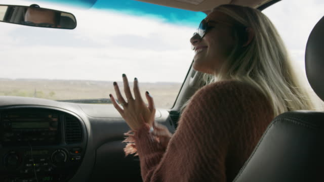 stockvideo's en b-roll-footage met woman passenger turning on radio in car and enjoying music / moore, utah, united states - voorruit
