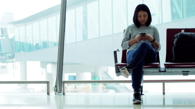 Woman passenger using smartphone in the terminal airport waiting for his flight