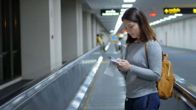 frau passagier mit travolator für go tor warten auf flug online einchecken per handy - laufband stock-videos und b-roll-filmmaterial