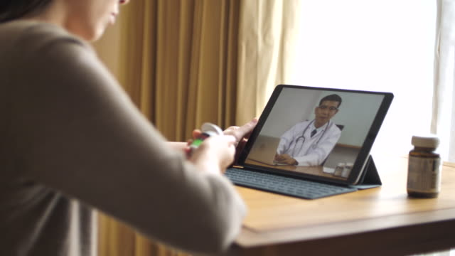 Woman patient talking to senior doctor on Digital tablet at home