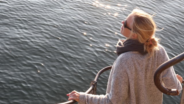 Woman pauses at railing, looks out over lake, surise