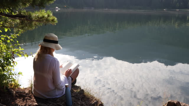 woman pauses at water's edge, looking off - 55 59 jahre stock-videos und b-roll-filmmaterial