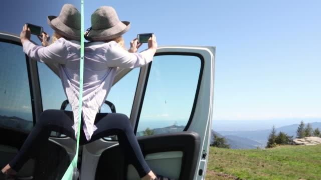 woman pauses beside campervan in meadow, mountains distant - leggings stock videos & royalty-free footage