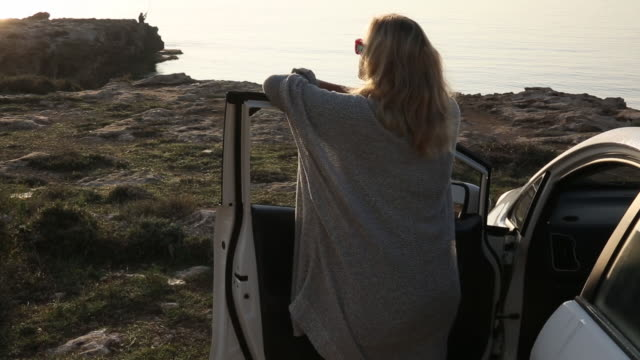 woman pauses beside car at sea cliff edge, look off - 景色を眺める点の映像素材/bロール