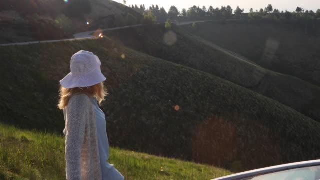 vidéos et rushes de femme s'arrête à côté de la voiture au lever du soleil, sur la route de montagne - quinquagénaire