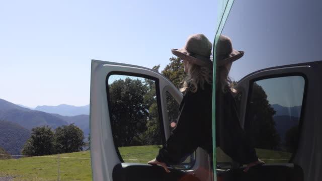 vídeos y material grabado en eventos de stock de mujer hace una pausa al lado de la puerta de la autocaravana - one mature woman only