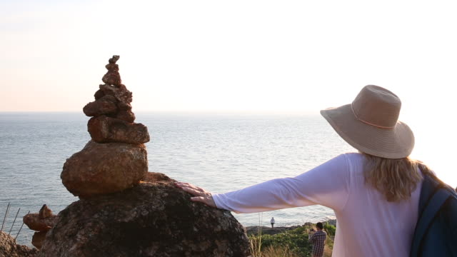 Woman pauses beside Zen rock piles, looks over sea