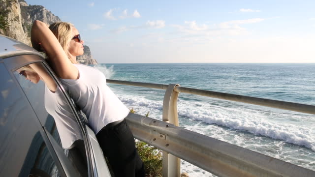 Woman pauses besides car, looks out to sea