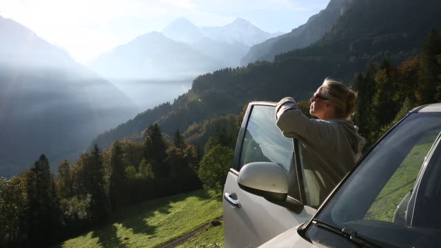 Woman pauses besides car to greet sunrise over mountains