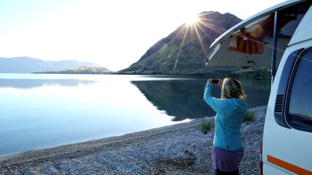 woman pauses by campervan at lakeshore, texting - lake stock videos & royalty-free footage
