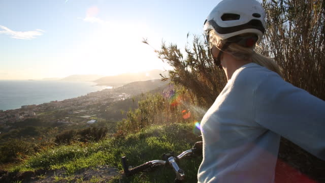 Woman pauses on hillcrest with bicycle above sea, village