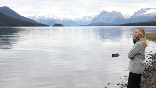Woman pauses on mountain lake shoreline