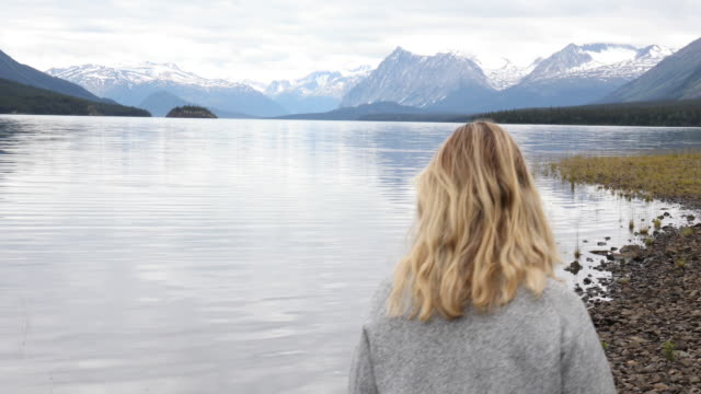 Woman pauses on mountain lake shoreline