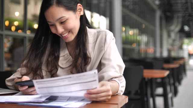 woman paying a bill online with smart phone - money back guarantee stock videos & royalty-free footage