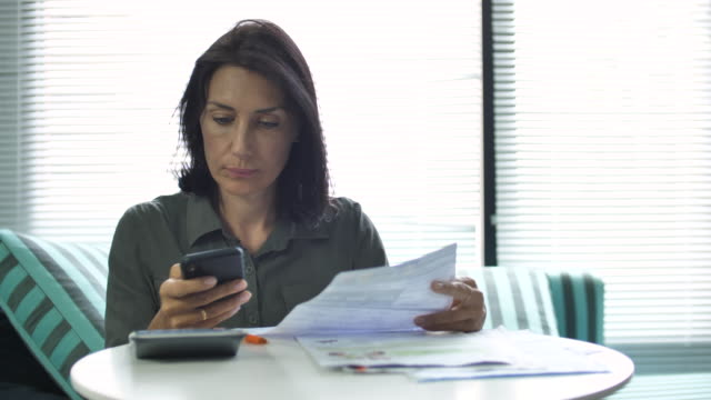 woman paying bill on smart phone at home - soft focus stock videos & royalty-free footage