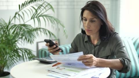 vídeos de stock, filmes e b-roll de mulher pagando bill telefone inteligente, pagamento móvel - frustração
