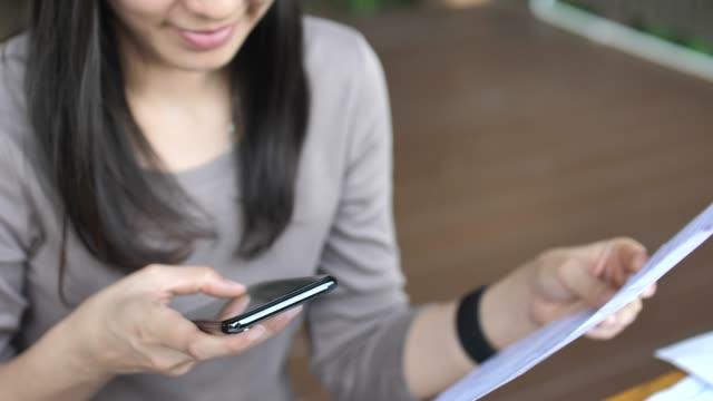 vídeos y material grabado en eventos de stock de mujer pagando factura en línea en su teléfono inteligente - factura