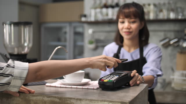 woman paying bill through smartphone using nfc technology - plain stock videos & royalty-free footage