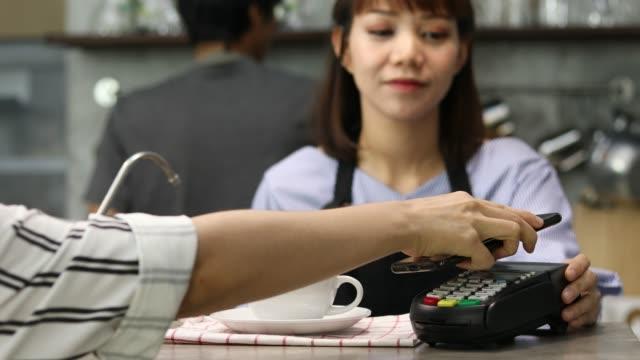 vídeos de stock, filmes e b-roll de mulher pagar através de smartphone usando tecnologia nfc - smart