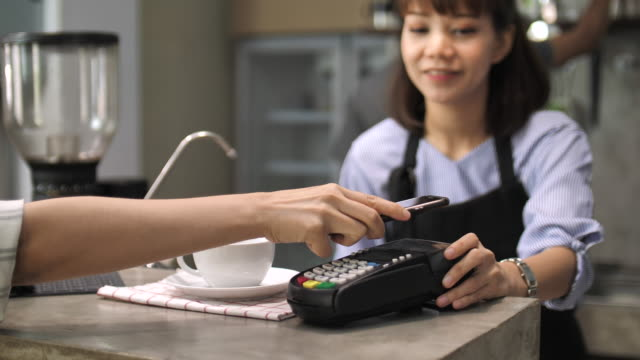 woman paying by mobile payment in cafe - paying stock videos and b-roll footage