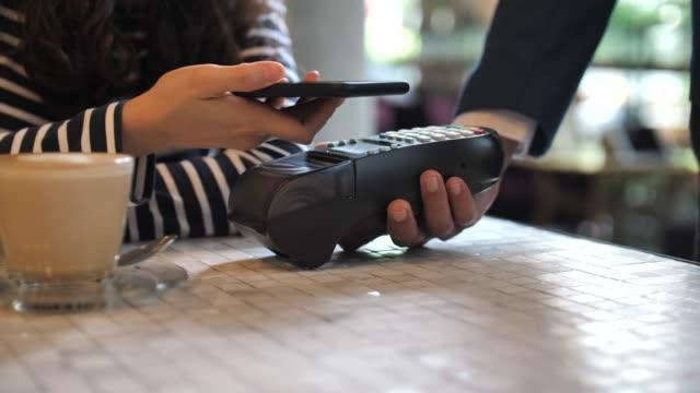 vídeos y material grabado en eventos de stock de mujer pagando por teléfono móvil con pago contactless en cafe - pago por móvil