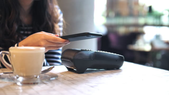 woman paying contactless payment on smart phone on cafe - money back guarantee stock videos & royalty-free footage