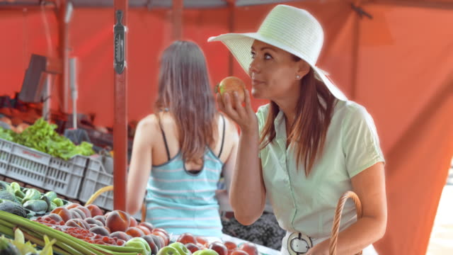 Woman paying for apples she picked out on market stall