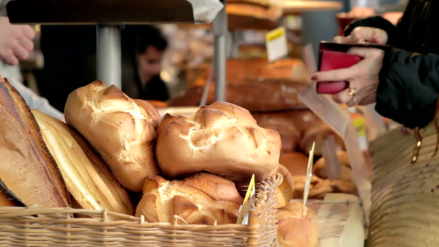 woman paying for bread - france stock videos & royalty-free footage
