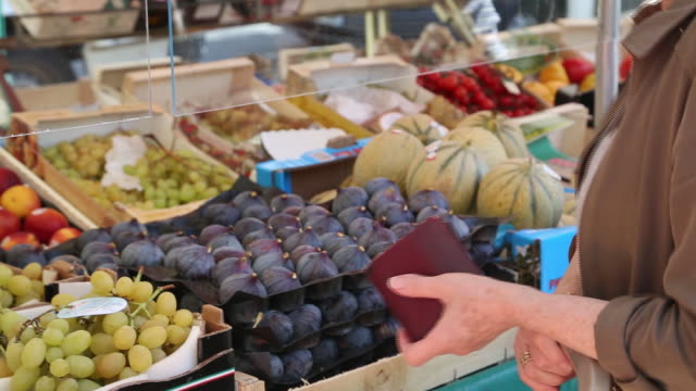 woman paying for fruits at street market in montparnasse, as pace of infections peaks up, in paris, île-de-france, france, on wednesday, september 9,... - currency stock videos & royalty-free footage